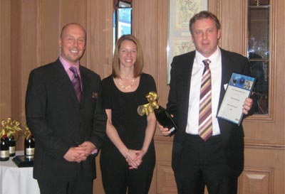 Frank Crouwel accepts award from Lora Wilson and Steve Gorski of Axis